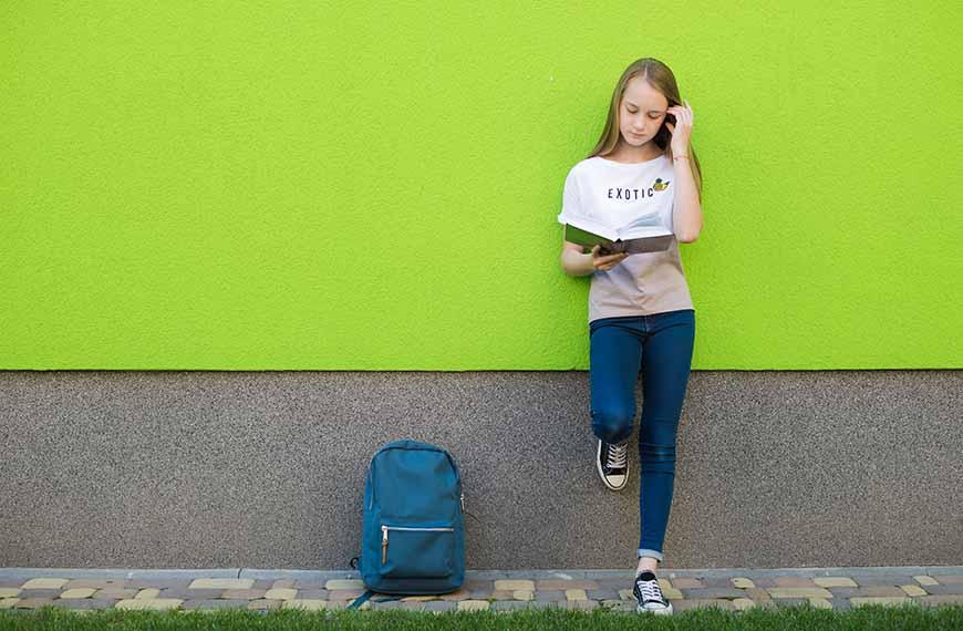 נערה נשענת על קיר ירוק עם מחברת ביד והילקוט לרגליה