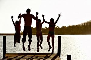 משפחה עומדת על גשר עם הגב למצלמה וקופצת באויר