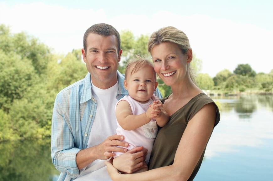 Couple with child standing by lake half length