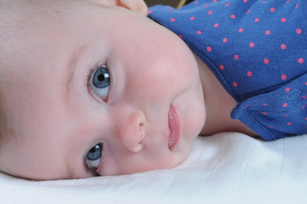 תינוקת שוכבת על הבטן ומסתכלת עלייך