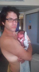אבא ללא חולצה מחזיק תינוקת על הידיים ומסתכל למצלמה