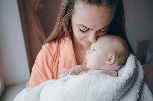 אמא מחבקת אליה את התינוק ומצמידה אליו את הפנים
