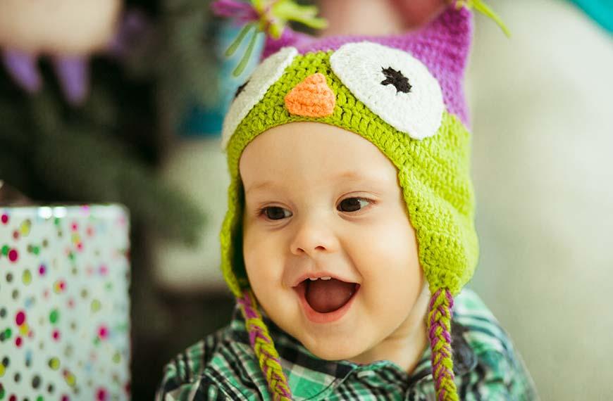תינוק צוחק עם כובע ינשוף צבעוני