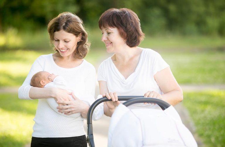 אשה מחזיקה תינוק ואמא שלה הולכת לידה עם העגלה