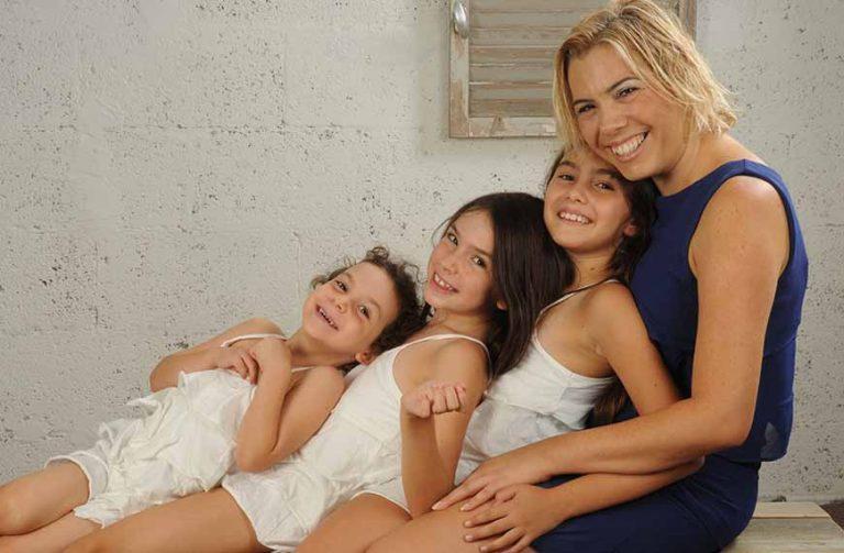 רוית שטרן גינת על ספסל ו3 הבנות שלה יושבות לפניה בשמלות לבנות