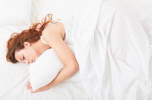 אשה שוכבת במיטה על הצד עם מצעים לבנים