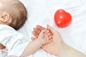 יד של תינוק על יד של אמא ולב אדום ליד