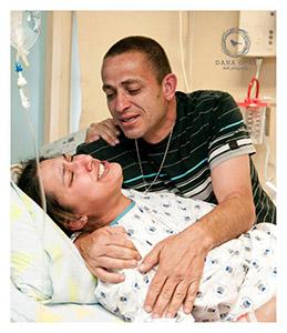 אשה בלידה על הגב ובן זוגה מחבק אותה