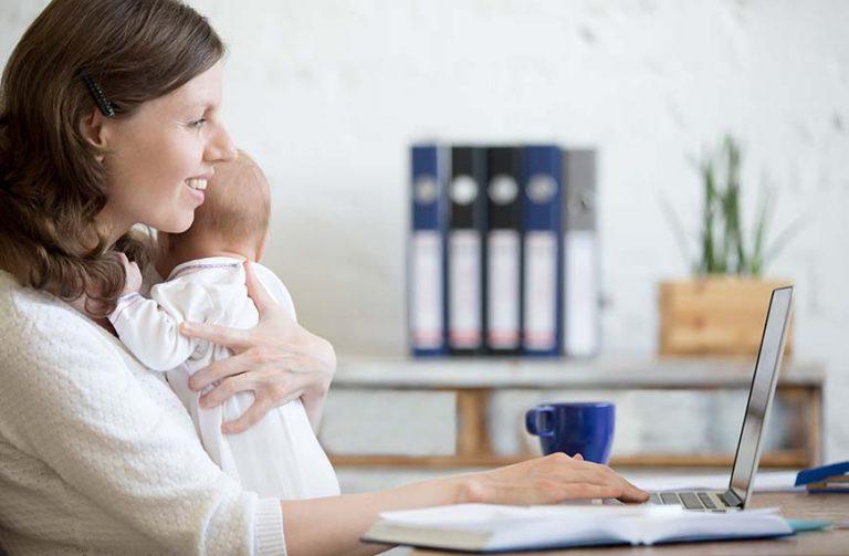 אמא יושבת על התינוק על הידיים ליד השולחן ועובדת על מחשב