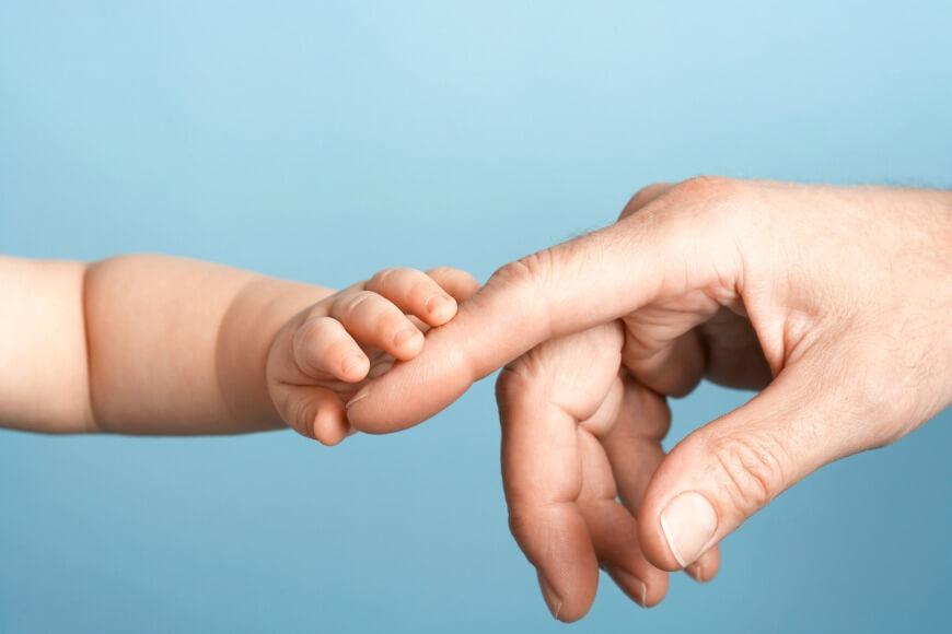 יד של תינוק נוגעת באצבע של מבוגר