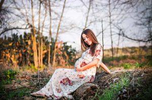 אשה הרה יושבת ומצטלמת ביער