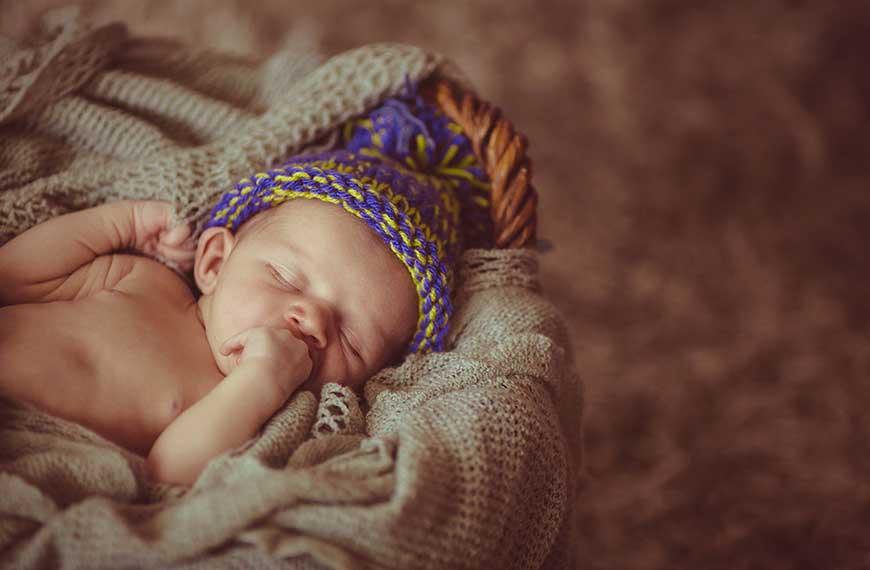 תינוק שוכב ערום עם כובע ויד בפה על מצע סרוג