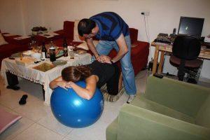 אשה שעונה על כדור לידה בעמידת שש ובן זוגה מתרגל עיסויים