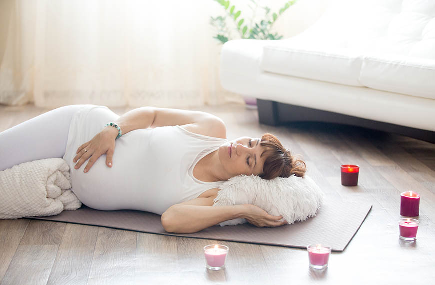 Pregnant woman relaxing after yoga practice in corpse pose at ho