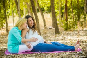 אשה בהריון נשענת על הדולה שלה בישיבה על הרצפה