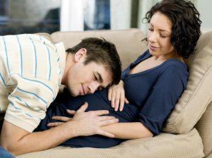 אשה בהריון על הספה ובן זוגה מניח ראש על הבטן