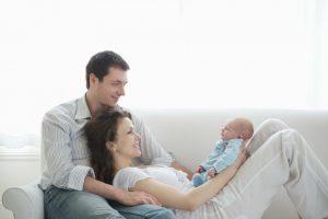 אמא שוכבת עם תינוק בחיקה ונשענת על האבא
