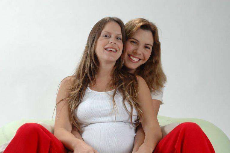 אשה בהריון יושבת ומחייכת והדולה מחבקת אותה מאחור