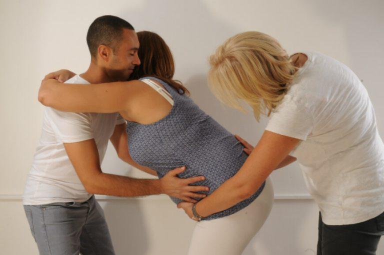 אשה הרה נשענת על בן זוגה והדולה מעסה אותה
