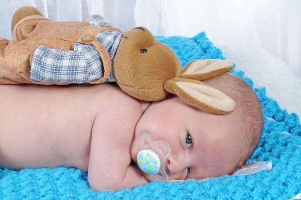 תינוק שוכב על הבטן עם מוצץ ועליו ארנב צעצוע