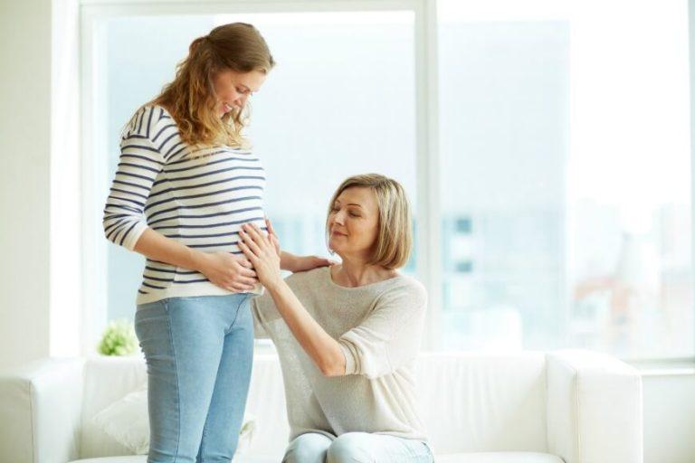 סבתא מניחה יד על הבטן של בתה בהריון