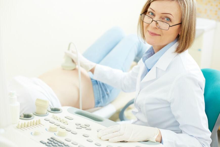 רופאה מבצעת בדיקת אולטראסאונד לאשה בהריון