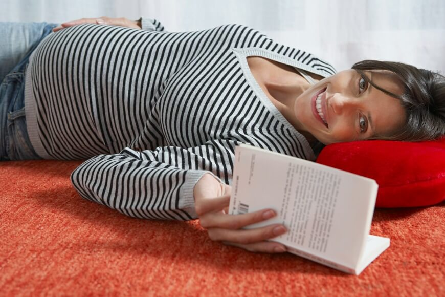 Pregnant woman lying on floor with book indoors