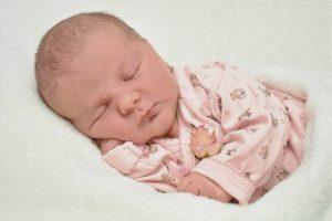 תינוקת ישנה על הצד לבושה בורוד
