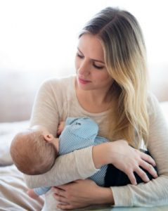 beautiful-young-mother-holding-her-baby-son-in-her-arms-sitting-on-bed
