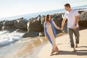 pregnant couple walking hand in hand on the beach)