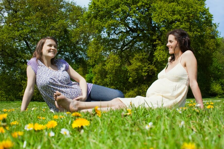 pregnant women sitting on the grass