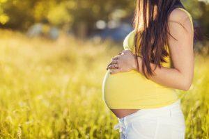 אשה בהריון בחולצה צהובה על רקע דשא
